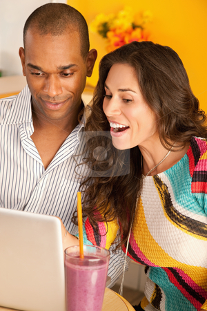 Couple on a Laptop stock photo, Young couple smile as they work on a laptop.  Vertical shot. by Scott Griessel