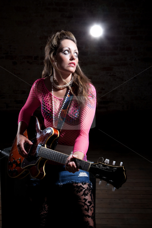 Punk Rock Girl stock photo, Young punk rocker tunes waits for cue to tune her guitar by Scott Griessel