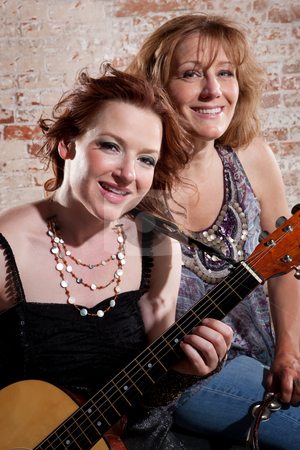 Female musicians stock photo, Ladies pose with guitar in front of brick background by Scott Griessel