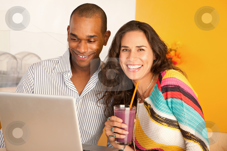 Couple With a Laptop stock photo, Young couple smile towards the camera while seated at a laptop and smoothie.  Horizontal shot. by Scott Griessel