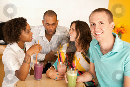 Group of Friends Talking stock photo, A group of young friends are socializing over smoothies.  One man is smiling at the camera.  Horizontal shot. by Scott Griessel