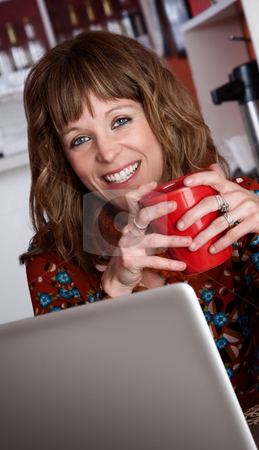 Pretty lady smiling stock photo, Pretty lady smiling with red ceramic mug at a cafe by Scott Griessel