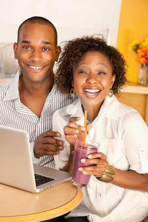Couple on a Laptop stock photo, Young couple smile as they work on a laptop.  The woman is holding a smoothie.  Vertical shot. by Scott Griessel