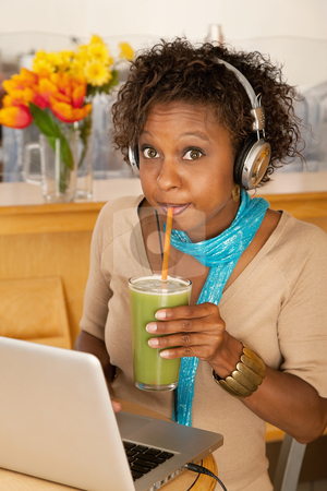 Young Woman Drinking Beverage and Using Laptop stock photo, A young woman sitting in a cafe and drinking a frozen beverage. She has a laptop open on the table in front of her and she is wearing headphones draped around her neck. Vertical shot. by Scott Griessel