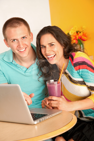 Couple With a Laptop stock photo, Young couple smile towards the camera while seated at a laptop.  The woman is holding a smoothie in her hand.  Horizontal shot. by Scott Griessel
