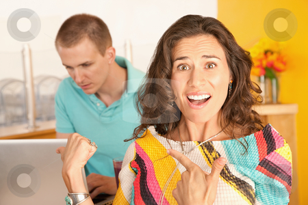 Angry Couple stock photo, Image of a woman in the foreground with a frustrated expression is pointing to a man in the background using a laptop. Horizontal shot. by Scott Griessel