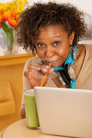 Young Woman Drinking Beverage and Using Laptop stock photo, A young woman sitting in a cafe and drinking a frozen beverage. She has a laptop open on the table in front of her and she has headphones draped around her neck. Vertical shot. by Scott Griessel