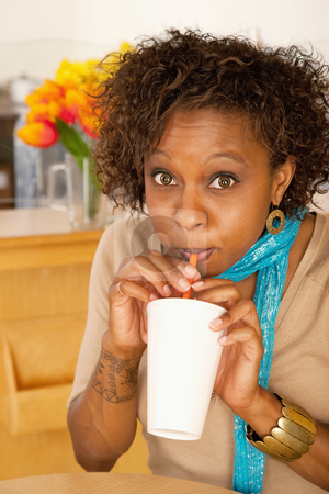 Woman Drinking Beverage stock photo, A woman is drinking a beverage from a cup and looking at the camera.  Vertical shot. by Scott Griessel