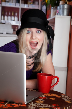 Surprised blonde stock photo, Surprised blonde girl with laptop and mug at a cafe by Scott Griessel