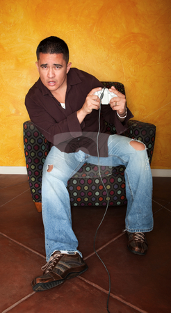 Man Playing Video Game stock photo, Handsome Hispanic man playing Video game by Scott Griessel