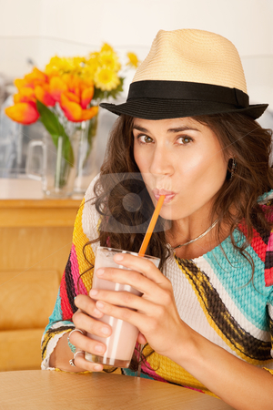 Woman Drinking a Smoothie stock photo, A woman is drinking a beverage from a cup and looking at the camera.  Vertical shot. by Scott Griessel