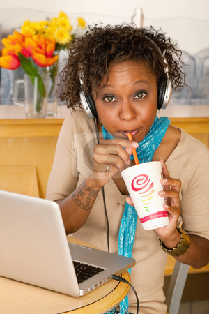 Young Woman Drinking Beverage and Using Laptop stock photo, A young woman sitting in a cafe and drinking a beverage. She has a laptop open on the table in front of her and she is wearing headphones draped around her neck. Vertical shot. by Scott Griessel