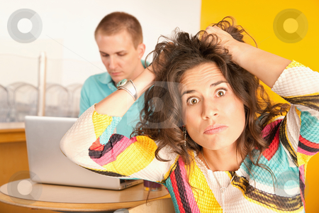 Woman Pulling Hair Out stock photo, Woman pulls at her hair in frustration while her boyfriend works on a laptop in the background.  Horizontal shot. by Scott Griessel