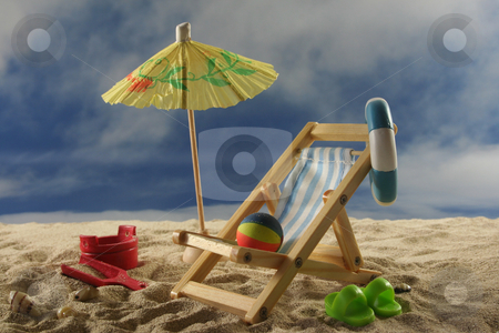 Holiday stock photo, Deck chair with sun umbrella, water polo and swimming ring on the beach by Mar&eacute;n Wischnewski