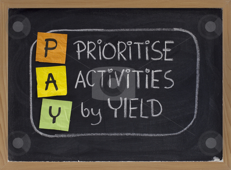 Prioritise activities by yield - PAY stock photo, PAY (prioritise activities by yield ) acronym, principle of working smart, color sticky notes and white chalk handwriting on blackboard by Marek Uliasz