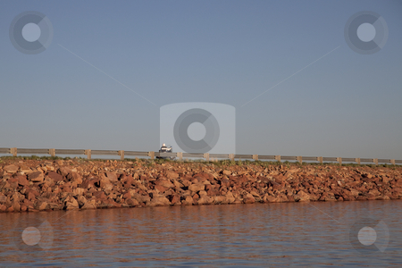 Highway on lake dam stock photo, Rock lake dam with highway and motorcycle in sunset light by Marek Uliasz
