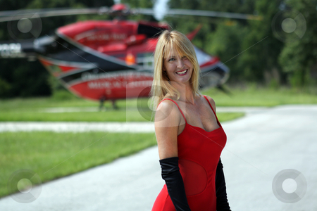 Woman in Front of a Helicopter (7) stock photo, A beautiful blonde dressed in a long red gown with long black gloves stands in front of a matching red and black helicopter. by Carl Stewart