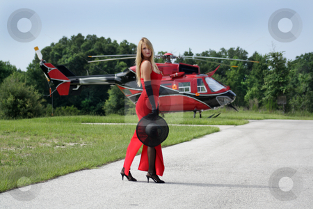 Woman in Front of a Helicopter (2) stock photo, A beautiful blonde dressed in a long red gown with long black gloves and holding a black hat stands in front of a matching red and black helicopter.  Full-length. by Carl Stewart