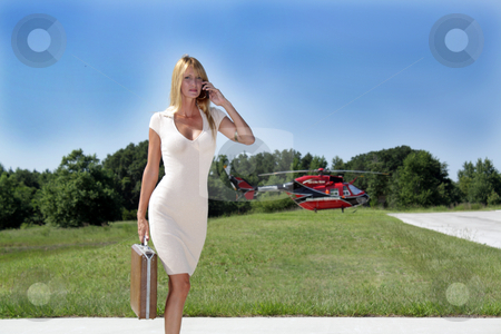 Businesswoman in Front of a Helicopter (2) stock photo, A beautiful blonde businesswoman holding a briefcase, talking on her cell phone, and wearing a cream-colored dress, stands in front of a red and black helicopter. by Carl Stewart