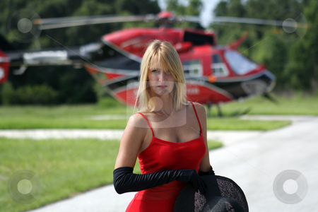 Woman in Front of a Helicopter (6) stock photo, A beautiful blonde dressed in a long red gown with long black gloves and holding a black hat stands in front of a matching red and black helicopter. by Carl Stewart