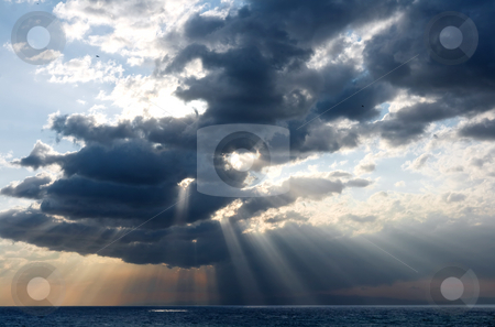 Rays and clouds stock photo, Rays of sun through the clouds over the sea by ANTONIO SCARPI