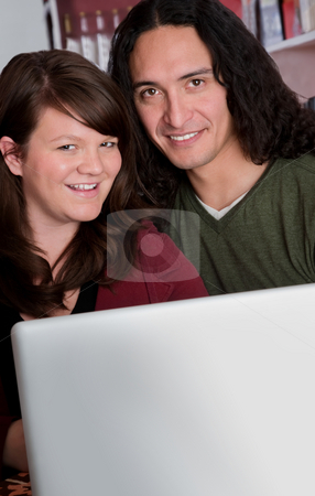 Interracial couple with copy space in front of laptop stock photo, Interracial couple with a laptop at a coffee house with copy space by Scott Griessel
