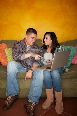 Hispanic Couple with Computer stock photo, Hispanic Couple on Green Couch with Computer by Scott Griessel