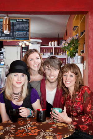 Four young happy friends at a cafe stock photo, Four young happy friends at a cafe by Scott Griessel