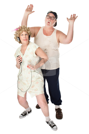 Funny Housewife Dancing in Front of Husband stock photo, Wife dancing to music with an annoyed husband by Scott Griessel