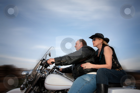 Couple riding a motorcycle stock photo, Middle-aged couple riding a motorcycle in the desert by Scott Griessel