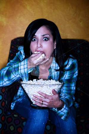 Pretty Hispanic woman with popcorn watching television stock photo, Hispanic woman with popcorn watching television by Scott Griessel