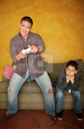 Man Playing Video Game with Bored Young Boy stock photo, Handsome Hispanic man playing Video game with bored young boy by Scott Griessel