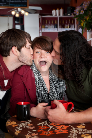 Lucky woman kissed by two handsome men stock photo, Lucky woman kissed by two handsome men in a cafe by Scott Griessel