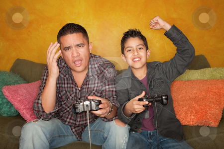 Hispanic Man and Boy Playing Video game stock photo, Attractive Hispanic Man and Boy Playing a Video Game with Handheld Controllers by Scott Griessel