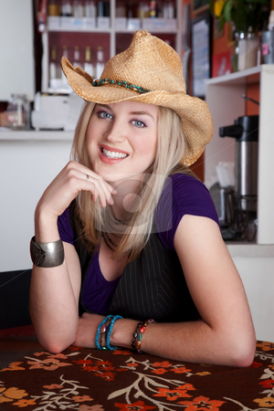 Smiling young blonde woman with cowboy hat in a cafe stock photo, Smiling blonde woman with cowboy hat in a cafe by Scott Griessel