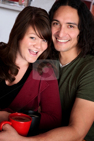 Attractive Couple with Coffee stock photo, Caucasian and Native American couple snuggling at a cafe by Scott Griessel