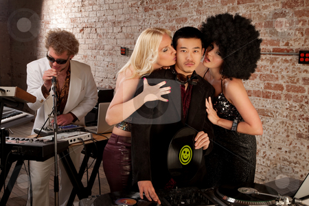 1970s Disco Music Party stock photo, Asian DJ with fan girls kissing his cheek by Scott Griessel