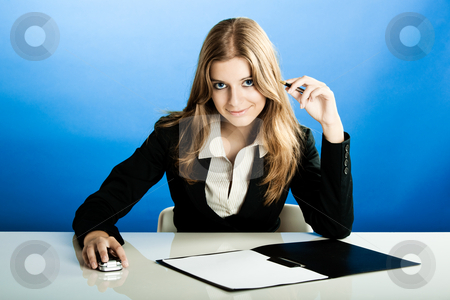 Business Woman stock photo, Portrait of a beautiful and business woman in the office doing some paperwork by ikostudio
