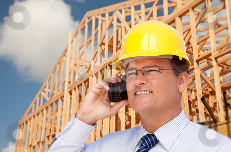 Contractor in Hardhat at Construction Site stock photo, Contractor in Hardhat at Construction Site Talks on His Cell Phone. by Andy Dean