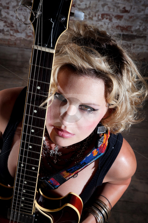 Female punk rocker stock photo, Female punk rocker with her guitar in front of a brick background by Scott Griessel