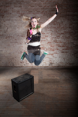 Female rocker stock photo, Young punk rocker jumps from a speaker in front of a brick background by Scott Griessel