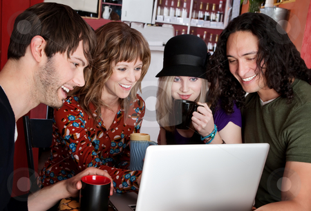 Four friends stock photo, Four friends laughing at content on a laptop by Scott Griessel