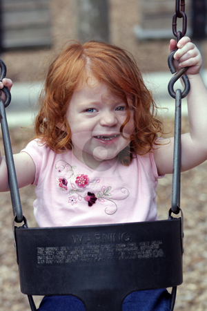 Cute Redhead Girl on a Playground (6) stock photo, An adorable two-year-old redhead girl on a playground swing looks directly at the camera with a smile. by Carl Stewart