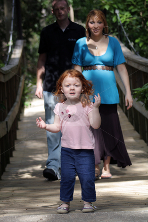 Family Outdoors on a Wooden Foot Bridge (2) stock photo, A young couple with their two-year-old daughter leading the way on a wooden foot bridge outdoors.  The mother is approximately 26 weeks pregnant. by Carl Stewart