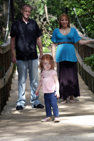 Family Outdoors on a Wooden Foot Bridge (1) stock photo, A young couple with their two-year-old daughter leading the way on a wooden foot bridge outdoors.  The mother is approximately 26 weeks pregnant. by Carl Stewart