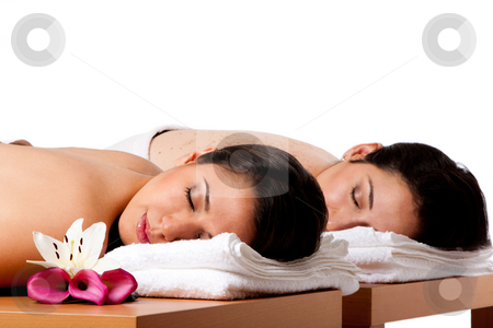 Women ready for spa massge stock photo, Two beautiful women friends laying on wooden tables with head on towels waiting for their massage in the spa, isolated. by Paul Hakimata