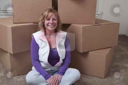 Moving in stock photo, Attractive Caucasian woman sits in front of a pile of boxes. by Christy Thompson