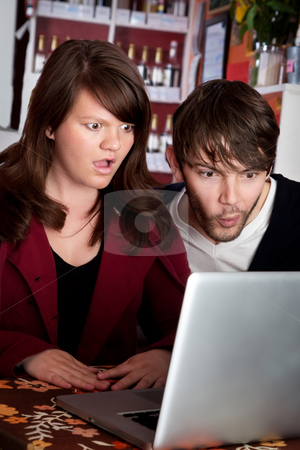 Woman and man staring with shock at laptop stock photo, Woman and man staring with shock at laptop computer by Scott Griessel