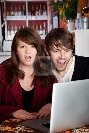 Shocked stock photo, Angry woman shocked with spouse over something on a laptop by Scott Griessel