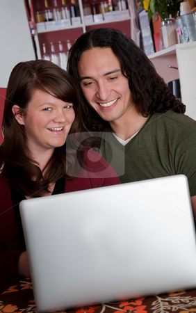 Interracial couple stock photo, Interracial couple with a laptop in a small cafe by Scott Griessel